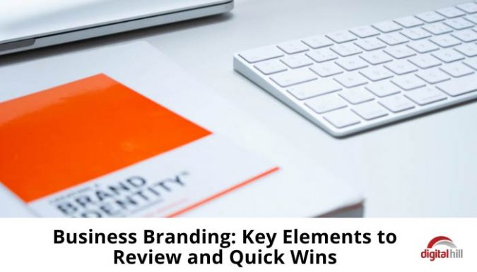 Orange business branding book lying next to a white keyboard on a white desk.